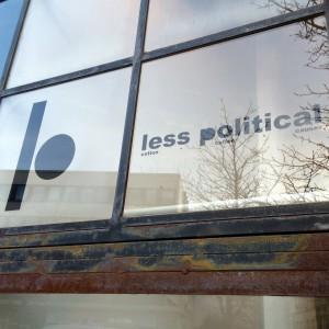 Logo und Less Political Schriftzug auf einem Fenster