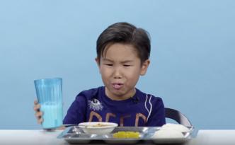Junge verzieht das Gesicht nachdem er eine weiße Flüssigkeit probiert hat beim Schulessen international