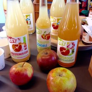 Flaschen mit leev Säften und einer Schorle, davor drei Äpfel