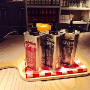 drei Dosen Olivenöl von Loui & Jules Bremen auf einem Brett mit kariertem Deckchen angerichtet