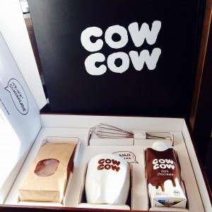 Box mit cow cow Becher, Trinkschokolade, Schneebesen und Schokolade