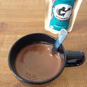 Tasse mit Trinkschokolade und koawach klassik Packung im Hintergrund