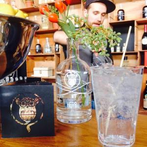 Gin and Tonic, Clockers Heft, Ginflasche als Blumenvase und der Barkeeper im Hintergrund