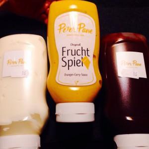 """eine Tube mit """"Fruchtspiel"""" Label, zwei umgedrehte Tuben mit Peter Pane Logo Label"""