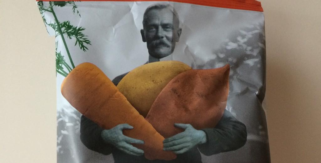 Schwarzweiß Bild eines Mannes der farbliches, überdimensional großes Gemüse in der Hand hält auf der Tyrrells Veg Crisps Packung