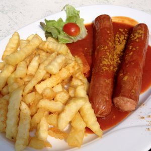 Teller mit Currywurst, geriffelten TK-Pommes, Salatblatt und halber Currytomate - Walsrode Restaurants