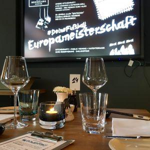 Tischgedeck, im Hintergrund der Screen mit #DeineFussballEuropameisterschaft