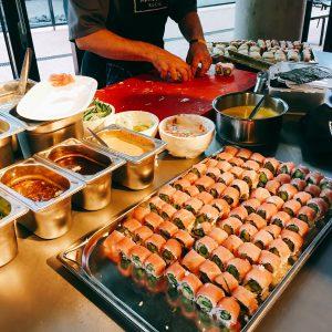 Großes Tablett mit Sushi, Zubereitung im Hintergrund
