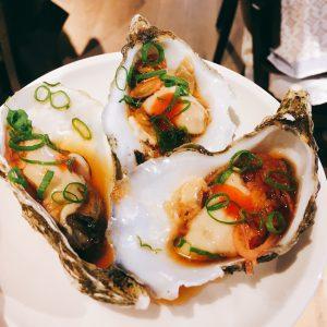Drei Austernhälften auf einem kleinen Teller