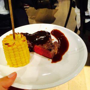 Halbes, medium gebratenes Steak und ein kleiner, gegrillter Maiskolben