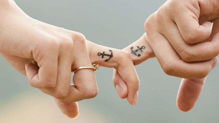 Sich haltende Zeigefinger mit Ankertattoos - Routine neu erleben