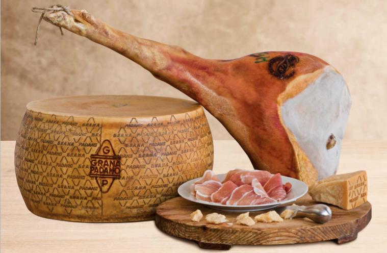 Prosciutto di San Daniele und Grana Padano Produkte im ganzen und zubereitet auf einem Holzbrett