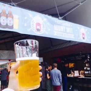 Pintglas mit Ratsherren Moby Wit Belgian White Ale vor selbigem Banner