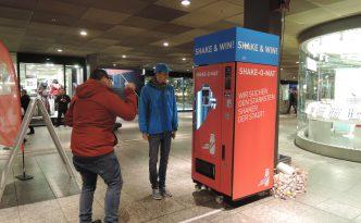 Der Actimel SHAKE-O-MAT am Bahnstieg mit tanzendem Mann davor