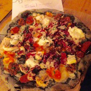Pizza mit Fleisch und Gemüse auf einem Weizen-Sepia Boden