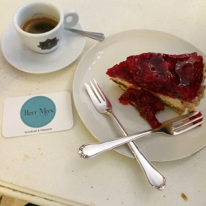 Obsttorte mit Espresso, Herr Max Visitenkarte und gekreuzte Gabeln
