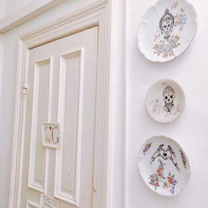 Toilettentür und Wand mit Tellern im Herr Max
