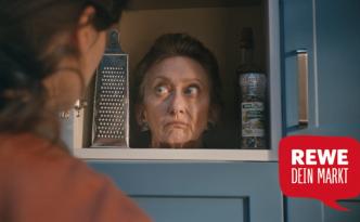 """Screenshot aus dem Clip """"Weihnachten 2016"""" von REWE - Kopf der Schwiegermutter im Küchenschrank"""