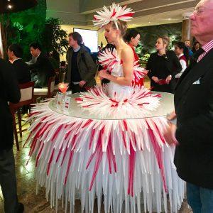 Frau steht in der Mitte des Tisches, der wie ein Kleid wirkt