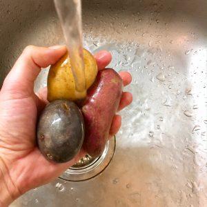 Kartoffel-Mix unter laufendem Wasserstrahl