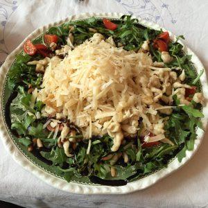 Parmesanspätzle auf Rucolasalat mit Pinienkernen und Cherrytomaten - ganzer Teller
