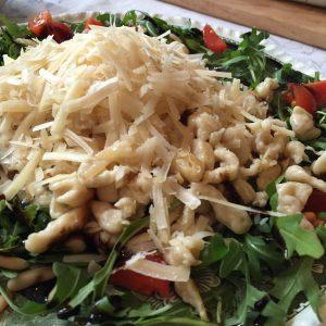 Parmesanspätzle auf Rucolasalat mit Pinienkernen und Cherrytomaten - Nahaufnahme