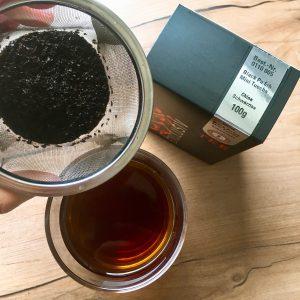 Tee im Sieb und Schwarztee im Glas