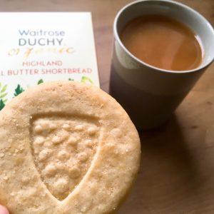Shortbread mit gestanztem Wappen vor Verpackung und Tee mit Milch