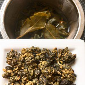 Oolong Tee in Kügelchen und als Blätter nach dem Aufguss